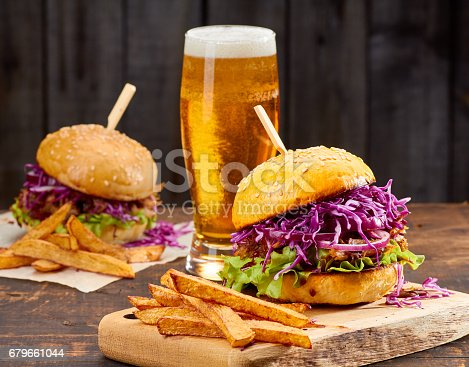 istock Two sandwiches with pulled pork, french fries and glass of beer on wooden background 679661044