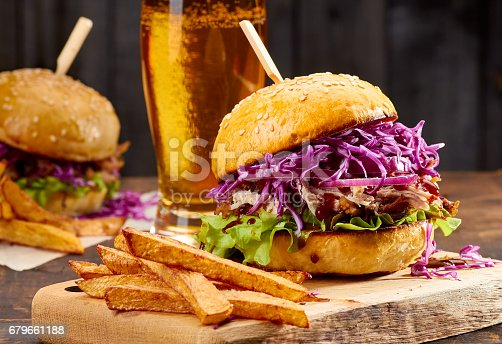 istock Two sandwiches with pulled pork, french fries and glass of beer on wooden background 679661188