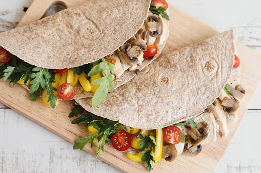 Two sandwiches with whole wheat wrap, chicken breast, mushroom and seasonal vegetables served on wooden board. Healthy and balanced meal