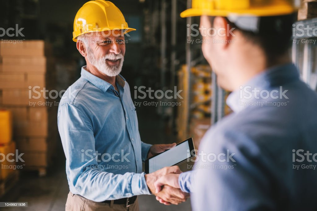 Two satisfied business man standing in warehouse with helmets on their head. Shaking hands and closing good job cooperation. stock photo