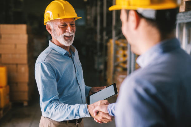 Two satisfied business man standing in warehouse with helmets on their head. Shaking hands and closing good job cooperation. Two satisfied business man standing in warehouse with helmets on their head. Shaking hands and closing good job cooperation. dealing cards stock pictures, royalty-free photos & images