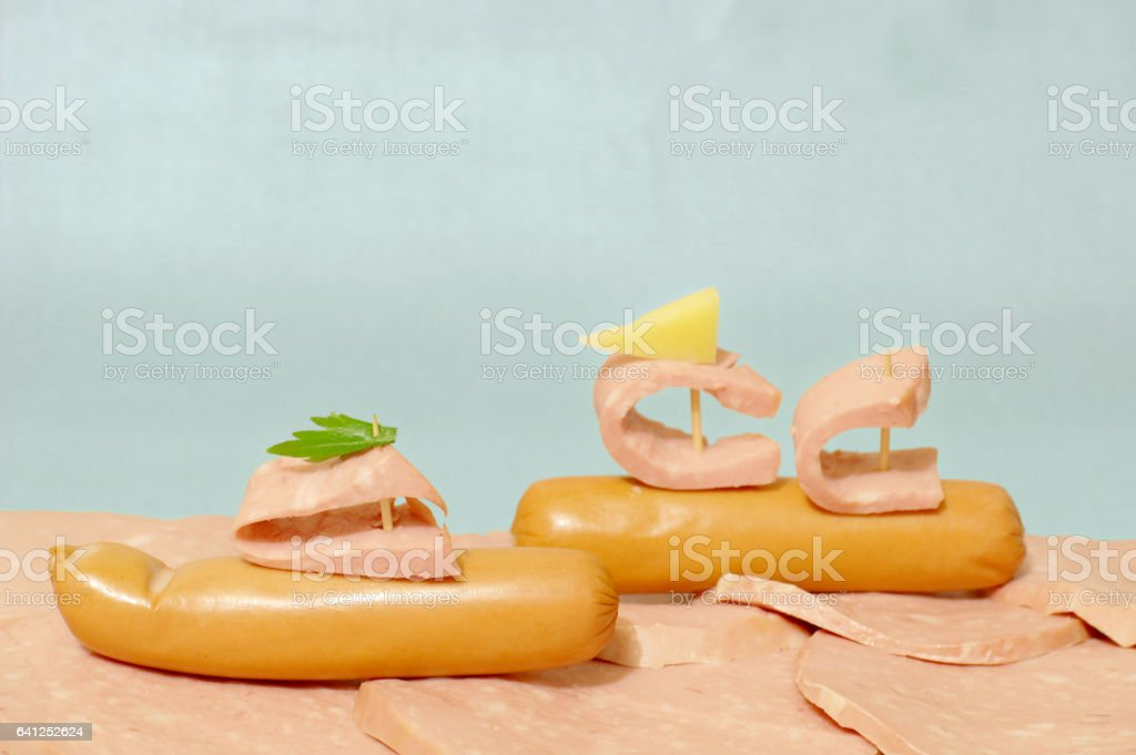 Two sausages as boats with sails and flags of the cheese and the parsley lie on the chunks of sausage with a fat stock photo