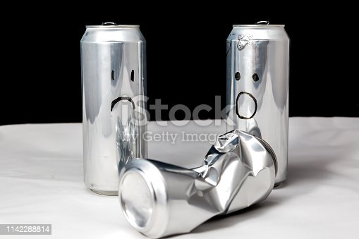 Two saw beaten one. Ð¡rumpled small can. Concept of people emotions. Aluminium can with drawed emoji of sadness and surprised