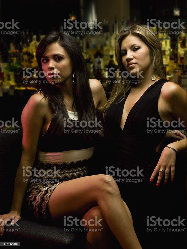 Two scantily clad, seductive women at a night club.  royalty-free stock photo