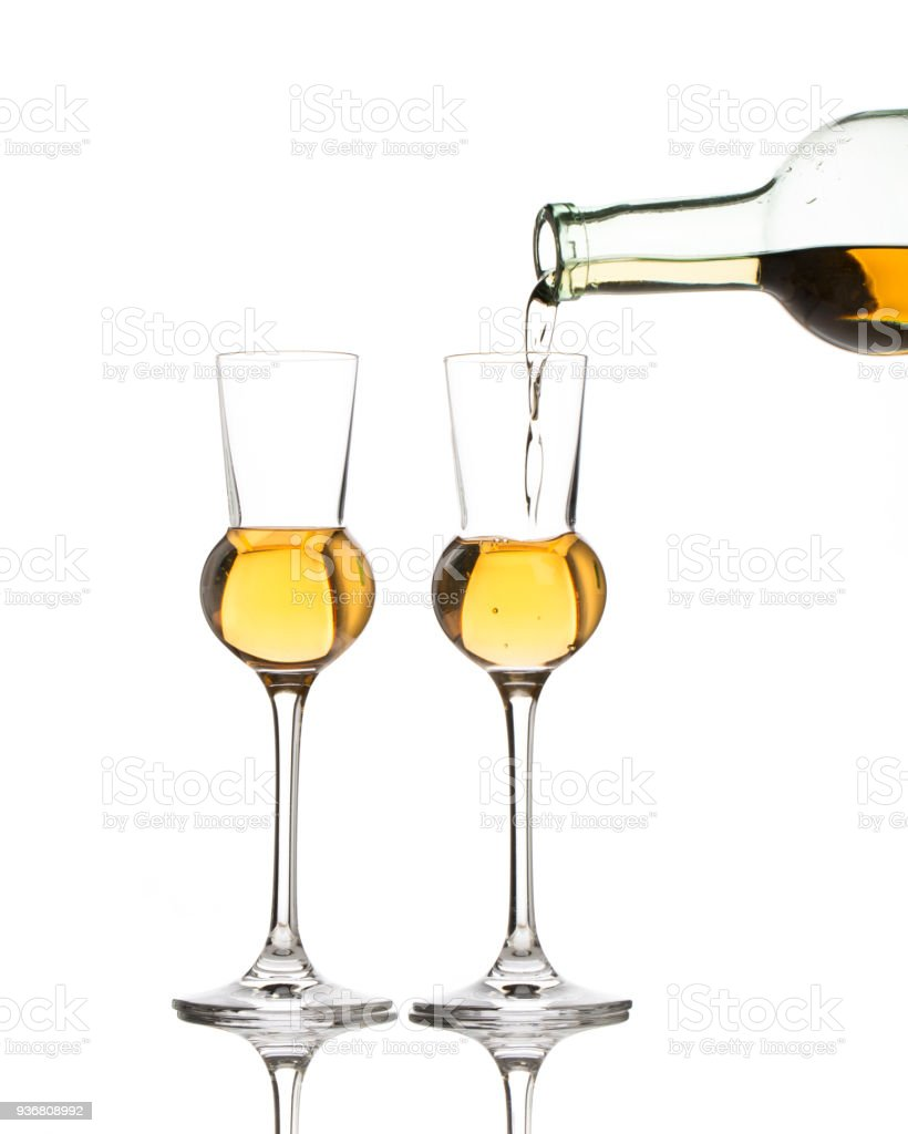 Two schnapps glasses are getting filled stock photo