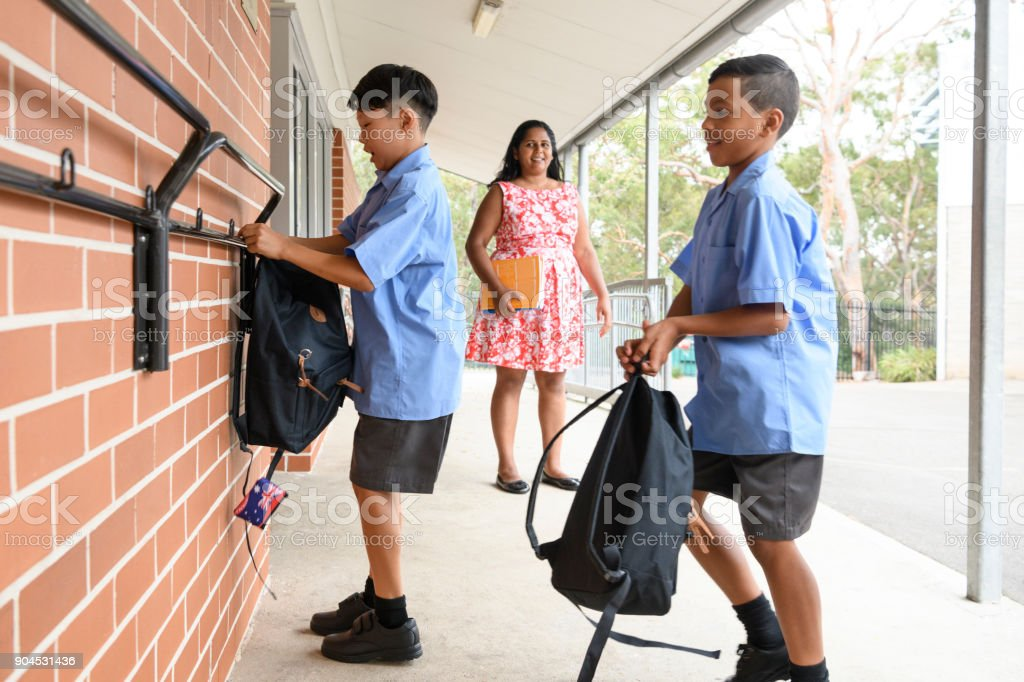Two school boys hanging backpacks up on pegs wall outside school stock photo