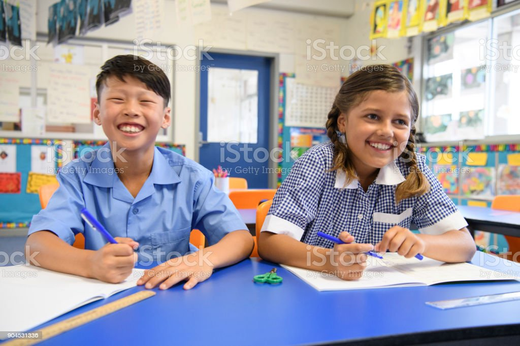 Two school children sitting next to each other in classroom and smiling stock photo