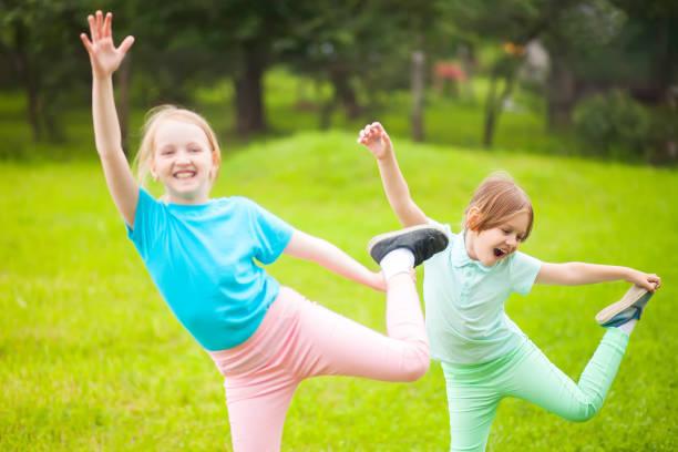 Two school girls doing exercises. stock photo