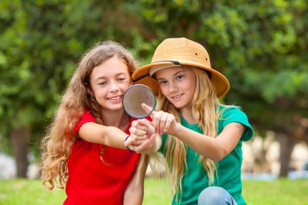 zwei schülerinnen erforschen die natur mit lupe - versuche nicht zu lachen stock-fotos und bilder