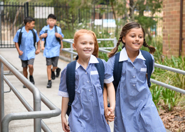 Two school girls holding hands on way to school stock photo