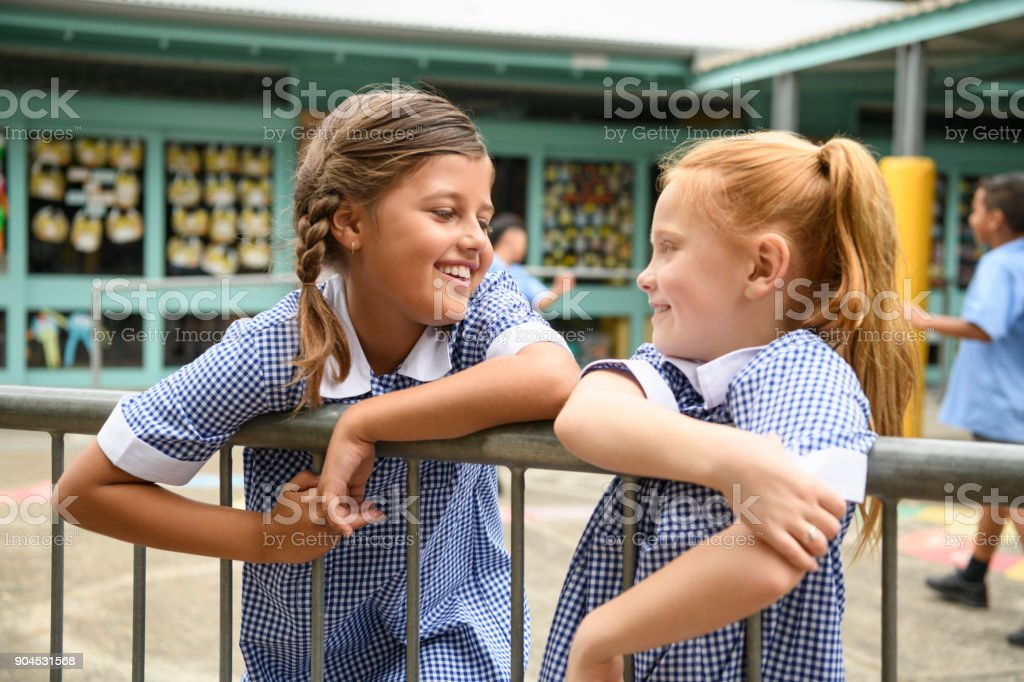 Two school girls leaning on railings in playground and chatting stock photo