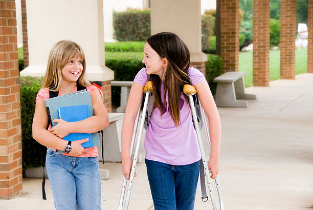 Two school girls, one carries books for her injured friend stock photo