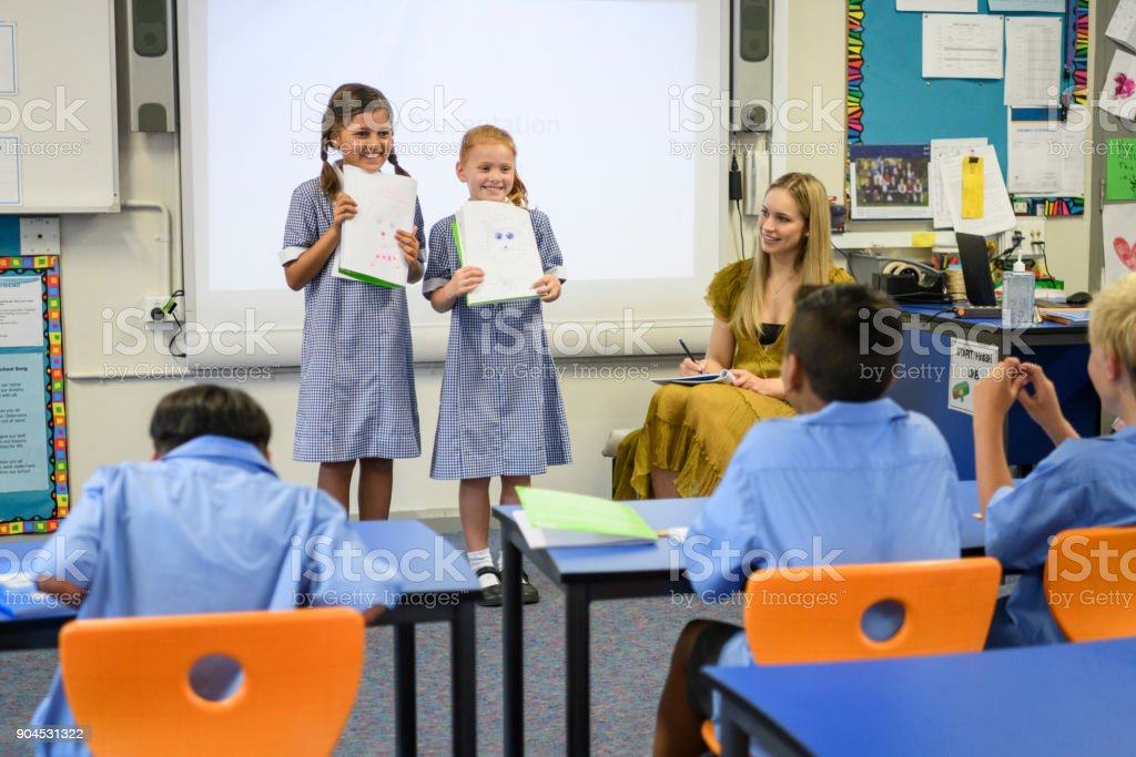 Two school girls presenting their work to the class with their teacher watching stock photo