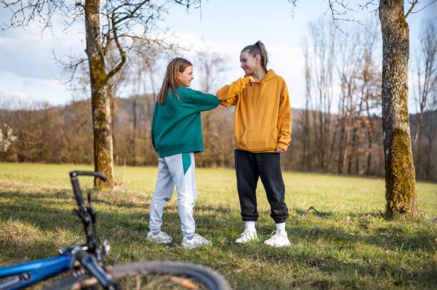 Zwei Schulmädchen mit Ellbogenstoß als alternativer Handschlag im Freien in der Natur – Foto