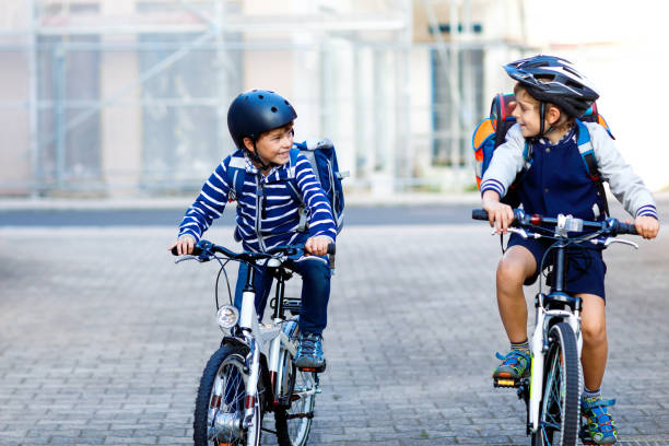 Two school kid boys in safety helmet riding with bike in the city with backpacks. Happy children in colorful clothes biking on bicycles on way to school. Safe way for kids outdoors to school stock photo
