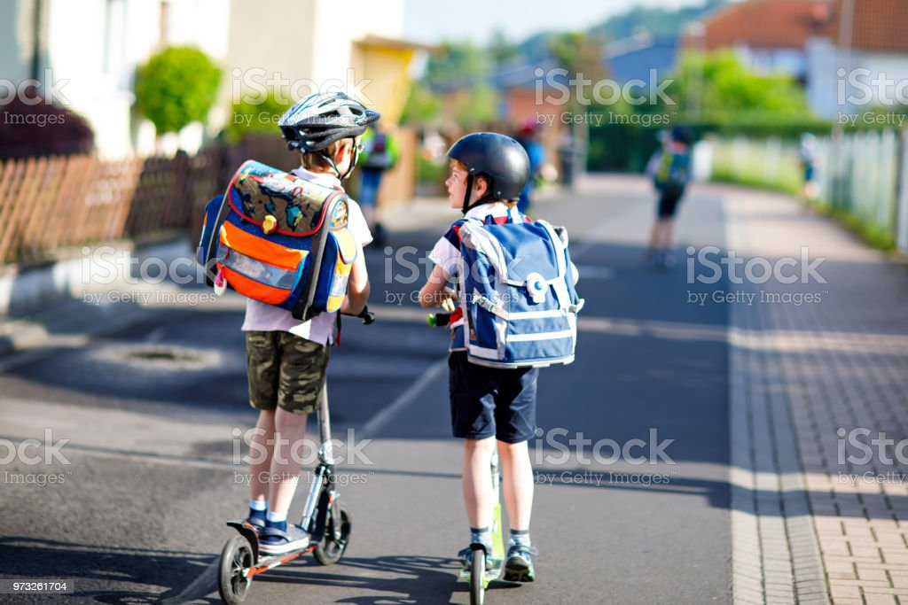 Zwei School kid jungen in Schutzhelm mit Roller in der Stadt mit Rucksack an sonnigen Tag Reiten. Glückliche Kinder in bunten Kleidern, Radfahren am Weg zur Schule. – Foto