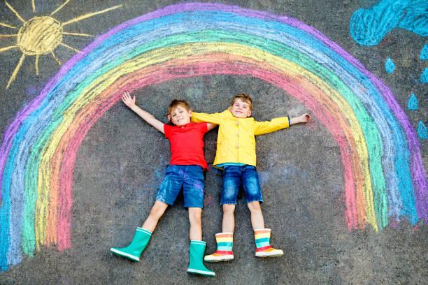 zwei Schulkinder Jungs Spaß mit mit Regenbogen-Bild-Zeichnung mit bunten Kreide auf Asphalt. Geschwister, Zwillinge und beste Freunde in Gummistiefeln malen auf dem Boden und spielen zusammen. – Foto