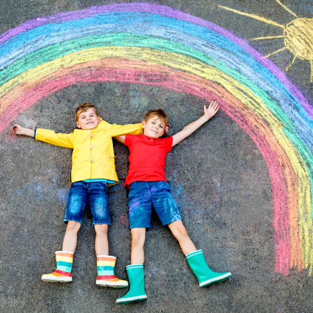two school kids boys with rainbow painted with colorful chalks on ground during pandemic coronavirus quarantine. Children painting rainbows along with the words Let's all be well. stock photo