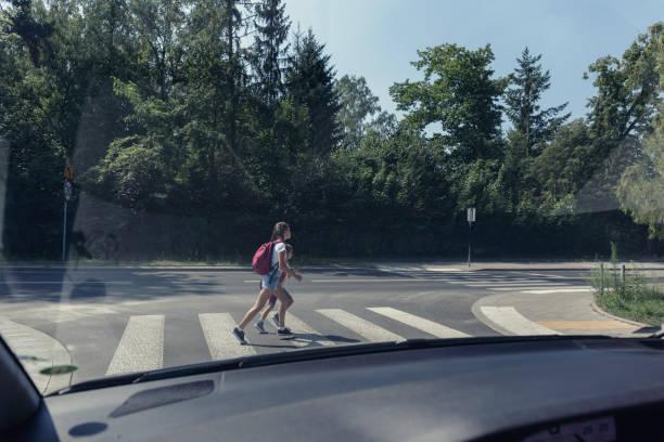 twee schoolkinderen op het zebrapad, uitzicht vanaf in de auto - oversteken stockfoto's en -beelden