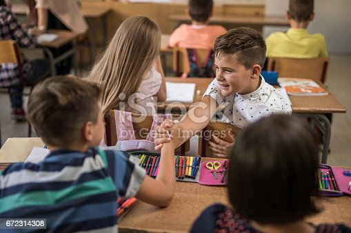 Two schoolboys greeting while sitting in the classroom stock photo two schoolboys greeting while sitting in the classroom stock photo more pictures of agreement istock m4hsunfo