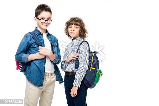 1016623732istockphoto two schoolboys with backpacks looking at camera isolated on white 1016623236