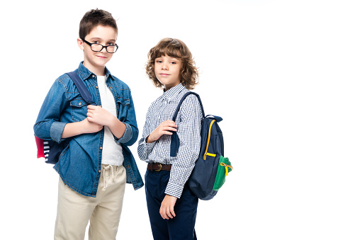 1016623732 istock photo two schoolboys with backpacks looking at camera isolated on white 1016623236