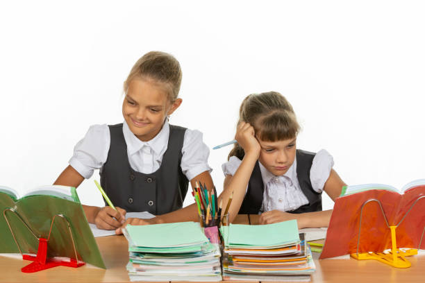 Two schoolgirls at a desk, one excellent student, the second two-year student Two schoolgirls at a desk, one excellent student, the second two-year student antipode stock pictures, royalty-free photos & images