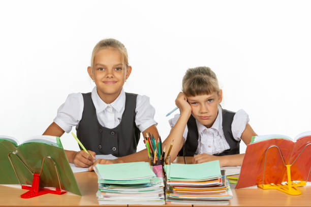Two schoolgirls at a desk, one funny, the other upset Two schoolgirls at a desk, one funny, the other upset antipode stock pictures, royalty-free photos & images