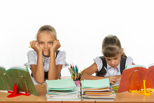istock Two schoolgirls at a desk, one leaning on her hands and looking into the frame, the other writes 1167332458