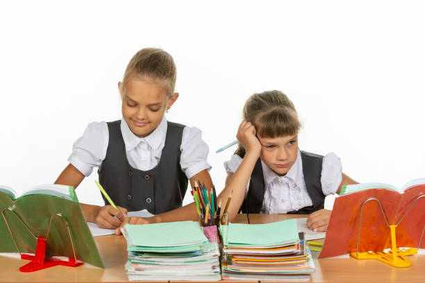 Two schoolgirls at a desk, one with a good mood, the other with a bad Two schoolgirls at a desk, one with a good mood, the other with a bad antipode stock pictures, royalty-free photos & images