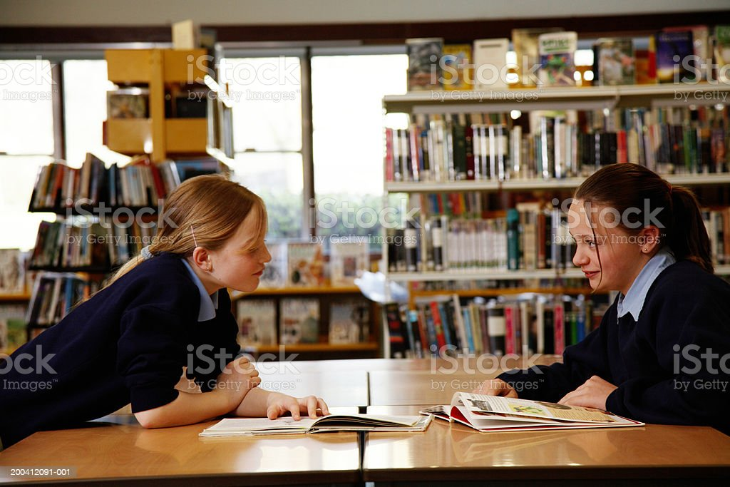 Two schoolgirls (11-13) smiling at each other across table in library royalty-free stock photo