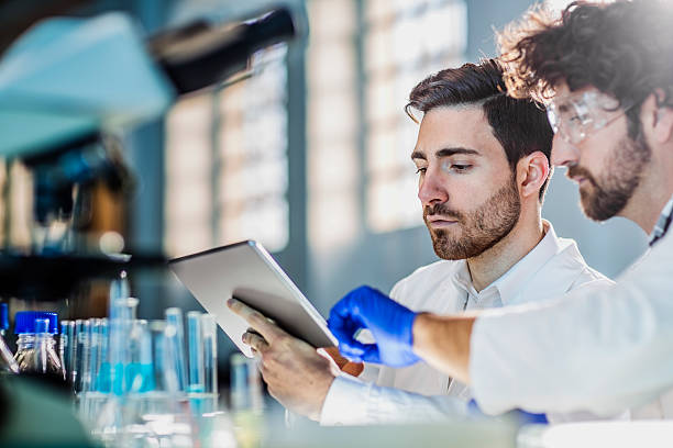 two scientist using digital tablet in laboratory - medical research stock photos and pictures