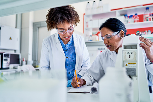 Two female scientists talking together and writing data in a notebook while working at a table in a lab