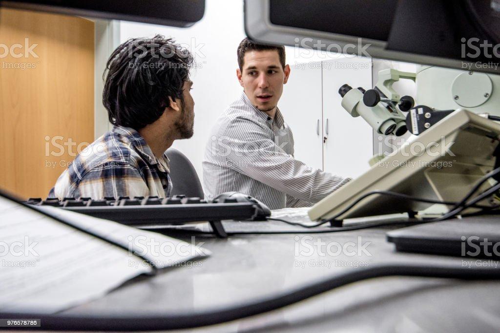 Dos científicos hablando de resultados de búsqueda de microscopio electrónico de emisión de campo - foto de stock