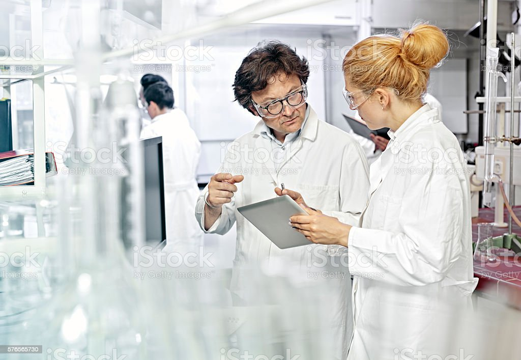 Two Scientists working on computer in a lab stock photo
