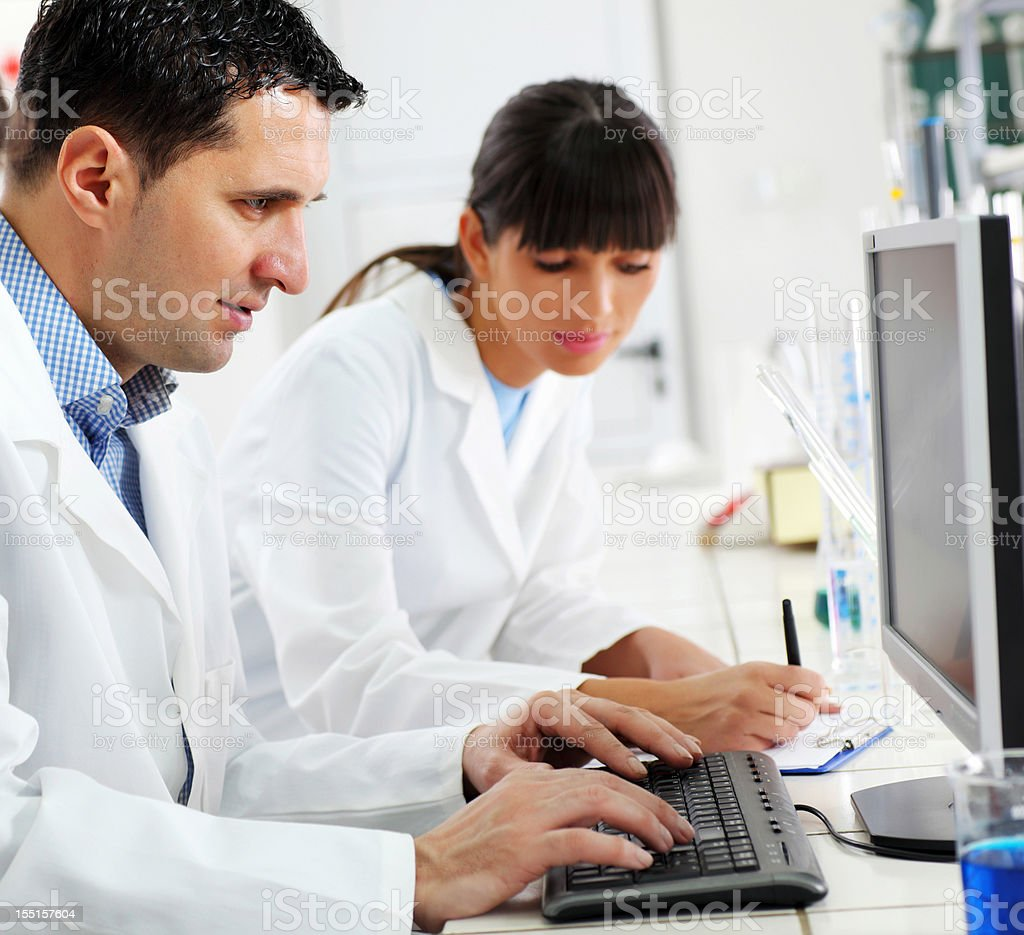 Two scientists working on computer in laboratory royalty-free stock photo