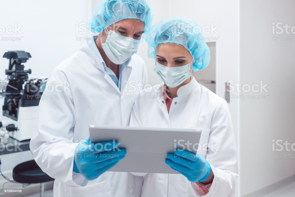 Two scientists working together in lab looking at data on a tablet...