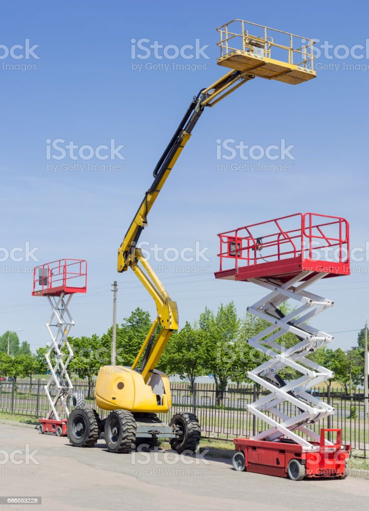 Two scissor and one articulated boom lift on asphalt ground royalty-free stock photo