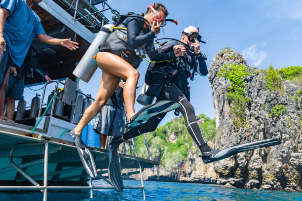 Two Scuba Divers jumping off boat into the sea holding hands stock photo