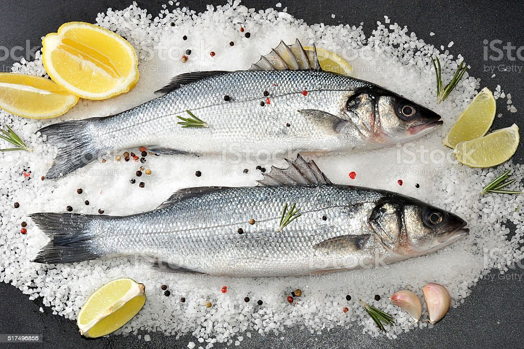 two seabass fish on salt with lemon and lime stock photo