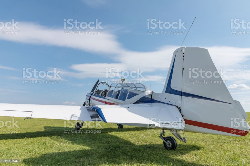 Two seat single engine civil utility aircraft, white small plane, red and blue strip is towed by a glider on a sunny day stock photo