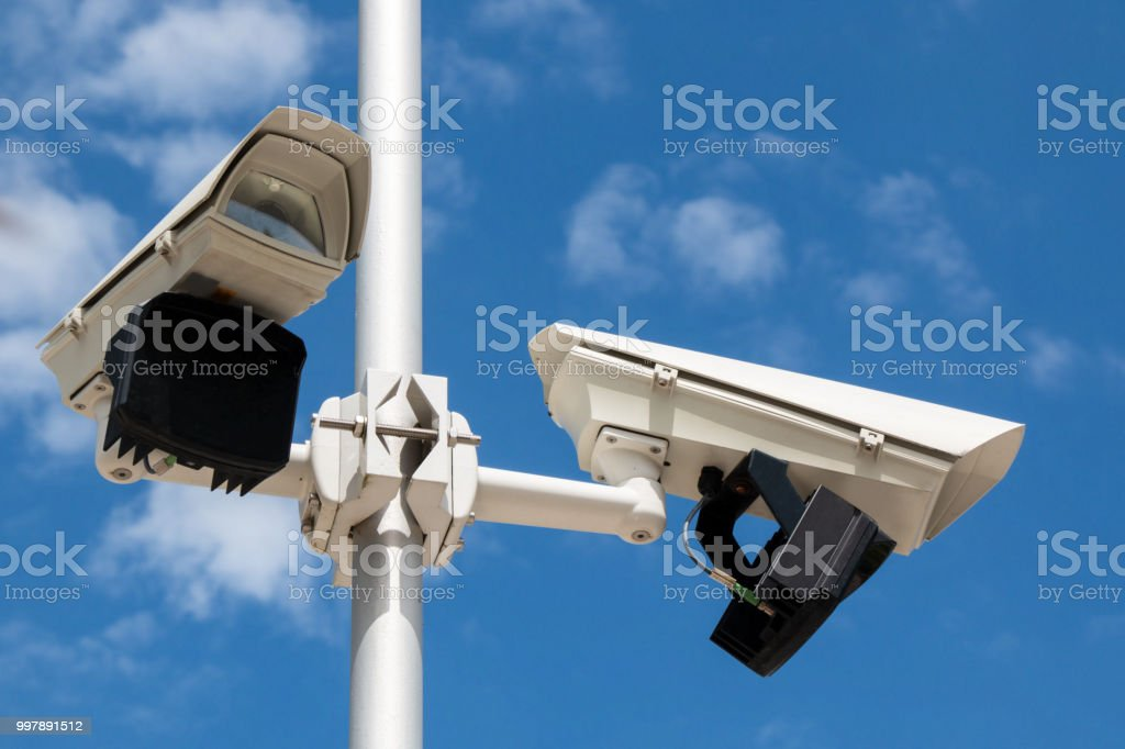 Two security cameras in front of blue sky stock photo