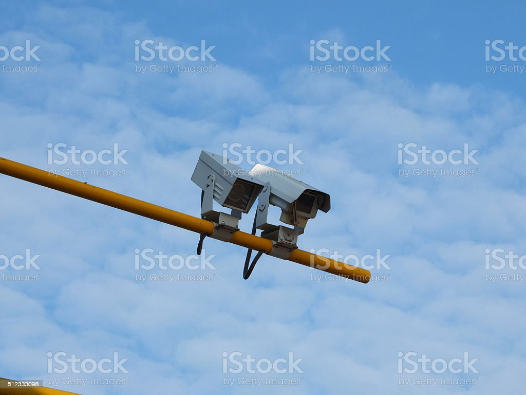 two security cameras on yellow pole with blue sky background stock photo