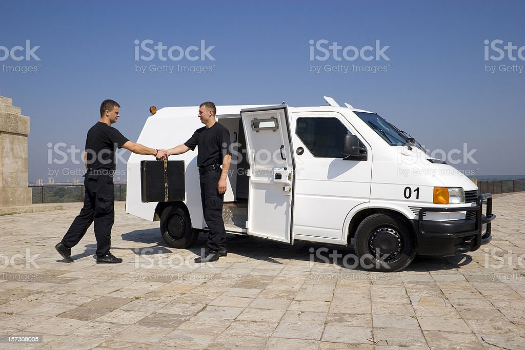 Two security members exchanging a case stock photo