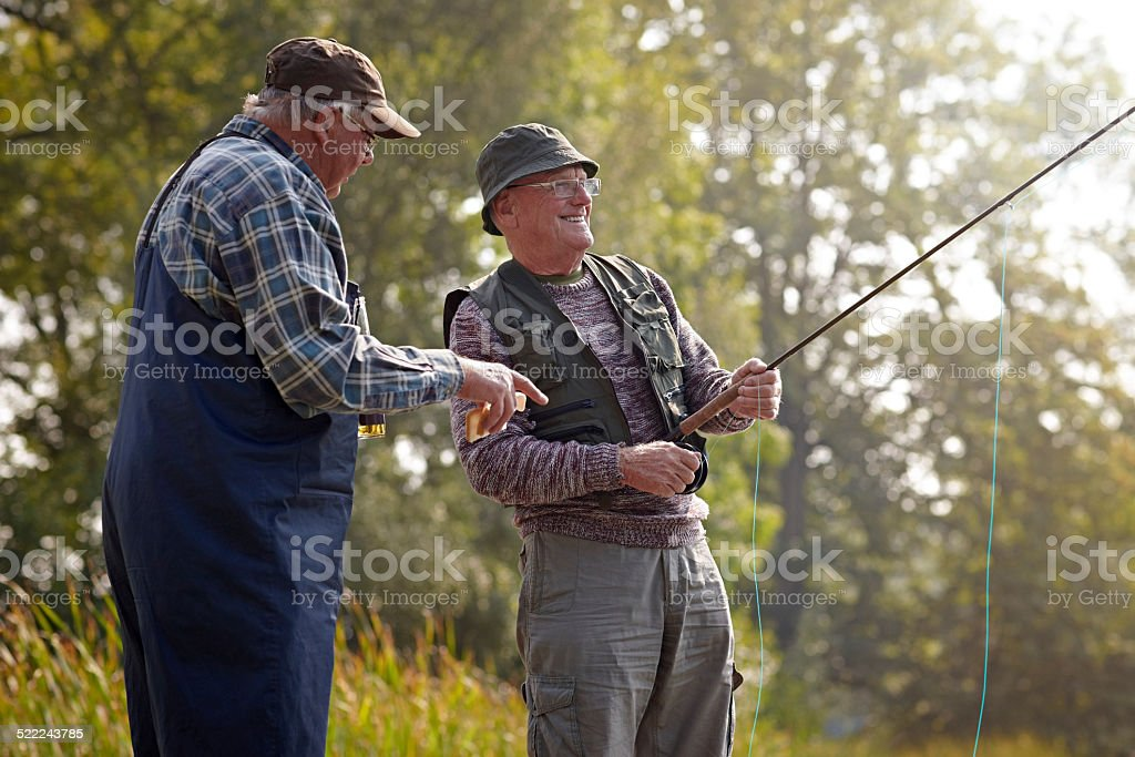Two senior adults fishing on lake stock photo