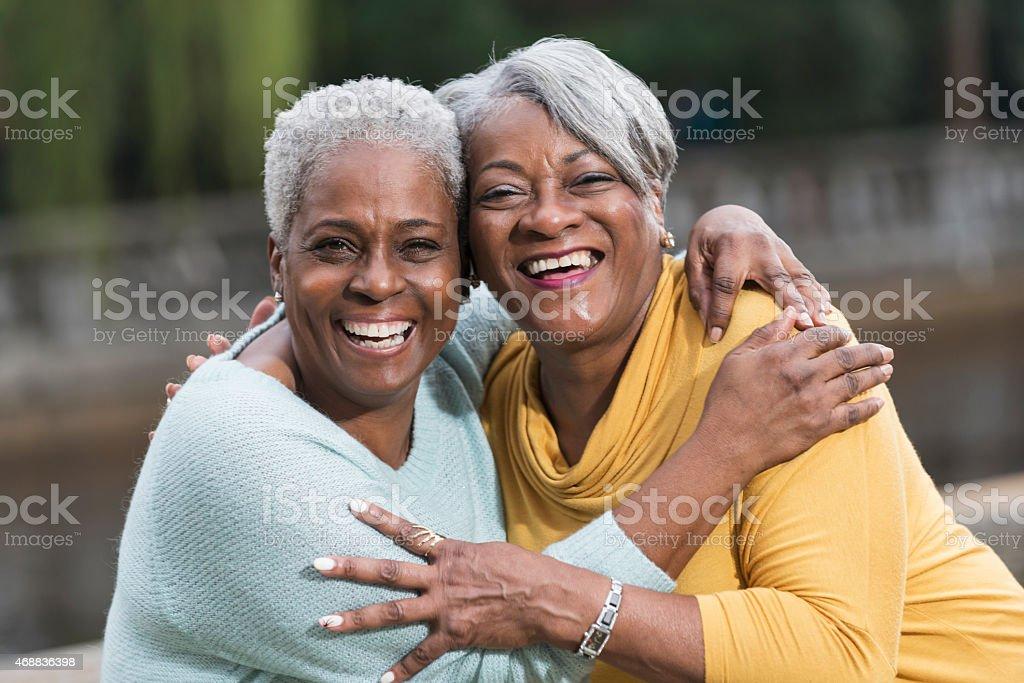 Two senior African American women hugging stock photo