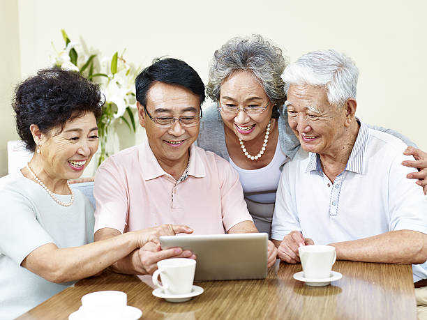two senior asian couple using tablet computer stock photo