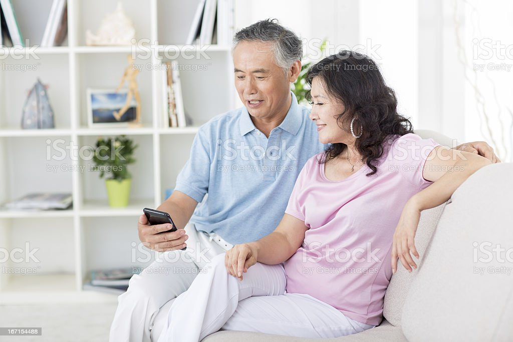 Two senior asian people looking at mobile phone stock photo