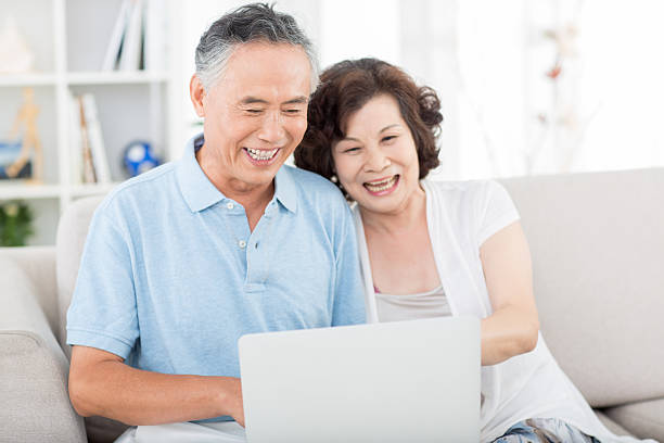 Two senior asian people using computer Two senior asian people at home shopping couple asian stock pictures, royalty-free photos & images