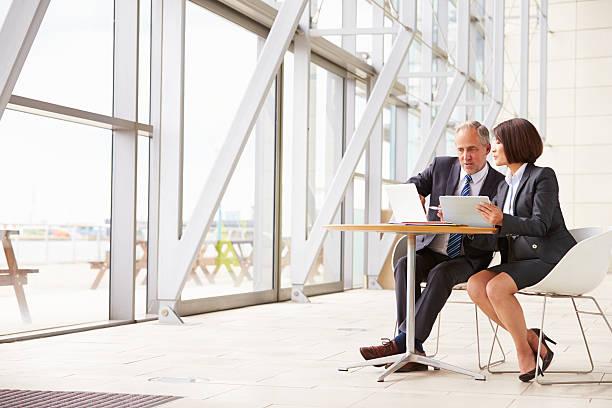 senior dois colegas de trabalho na reunião no interior moderno - senior business woman tablet imagens e fotografias de stock